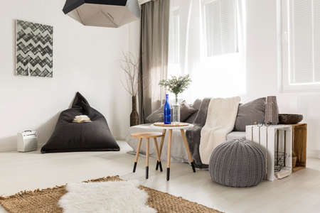 Light livng room with bean bag, comfortable sofa, DIY table, window and stylish decorative details