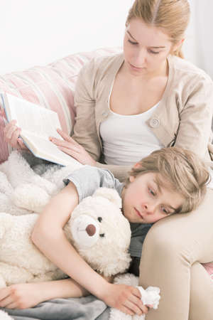 boy kid: Shot of a young woman reading a book to her sick son