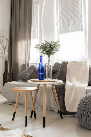 Moderne woonkamer met een bank, poef, nieuwe bijzettafels, raam en stijlvolle decoraties Stockfoto