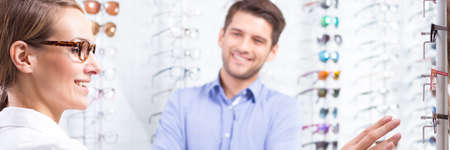 style advice: Female optician doctor presenting eyeglasses to handsome man