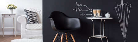 coffees: Cozy space with black wall and white coffee table with two coffees with milk on it. In the background white sofa in room