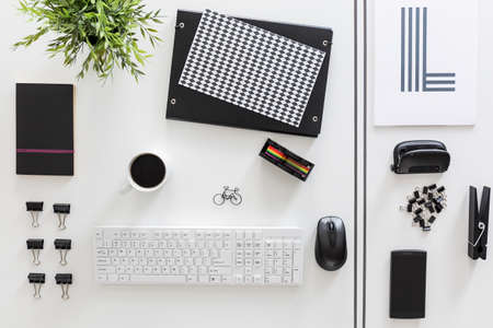 White desktop with esthetically ordered white and black stationery Stock Photo