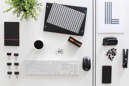 Witte bureaublad met esthetisch bestelde witte en zwarte briefpapier Stockfoto
