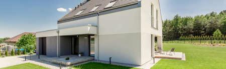 Außenansicht eines modernen Hauses mit Garage, Terrasse und Garten Standard-Bild