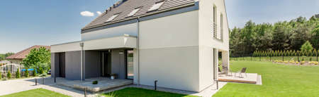 Exterior view of a modern house with garage, patio and garden