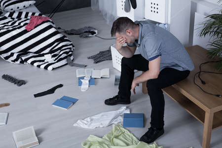 burglary: Despair man covering his face and his apartment after burglary Stock Photo