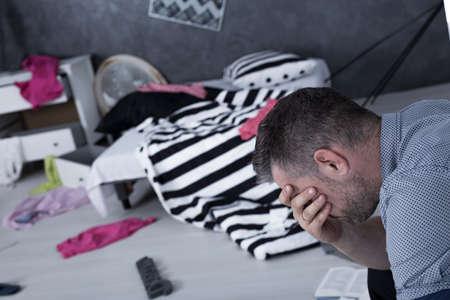 Prise de vue d'un homme de désespoir couvrant son visage et sa chambre après le cambriolage