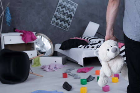 robbed: Close up of a man holding a teddy bear looking at chaos in his house Stock Photo