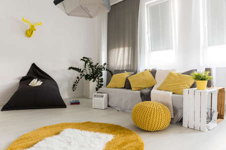 Light interior in new style with bean bag chair, carpet, sofa, pendant lamp, DIY side table, window, and yellow details
