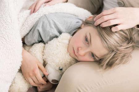 chory: Ujęcie smutnego chorego chłopca trzymającego głowę na kolanach matki