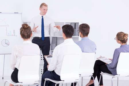 動機上の訓練中に従業員のグループに話しているホワイト ボードの横に立っているハンサムな男 写真素材