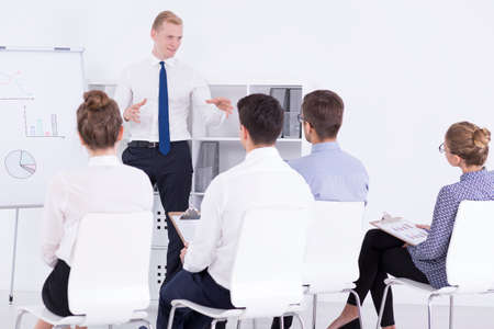 Handsome man standing next to a whiteboard talking to a group of employees during motivational training