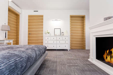 comfort room: Modern and spacious bedroom with fireplace, big bed, white commode and new wooden doors