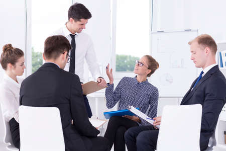 会議中に光のインテリアに座っている肯定的な企業の労働者のグループ