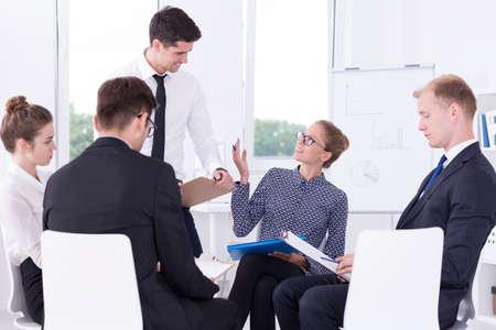 Grupa pozytywnych pracowników korporacyjnych siedzi w jasnym wnętrzu podczas spotkania