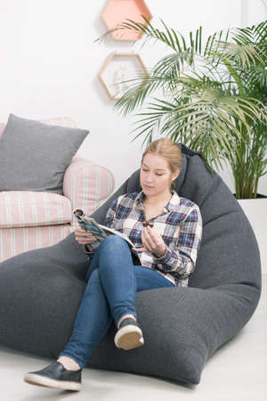 beanbag: Shot of a young woman sitting on a bean bag in her room and reading a magazine