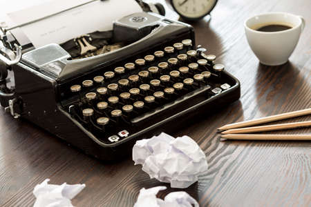 writes: Novelists workplace with the typewriter, pencils, creased papers and coffee on