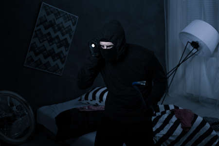Burglar wearing black clothes holding a flashlight breaking into a house at night
