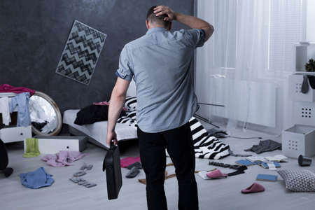 Man back view and chaos in apartment after burglary