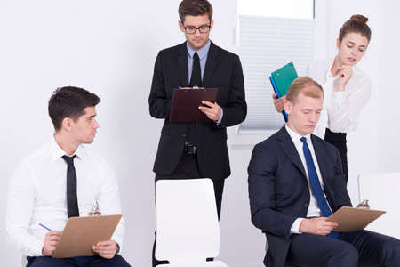 Two men writing qualification test, two HR specialists standing over them, light interior Stock Photo