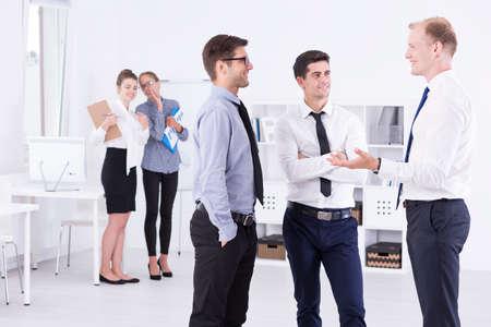 acoso laboral: Grupo de tres hombres de negocios hablando juntos en una oficina de la luz, en el fondo de dos mujeres hablando de ellos Foto de archivo