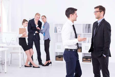 acoso laboral: Dos hombres elegantes que hablan en una oficina de la luz, en el grupo de fondo de tres trabajadores ridiculizando nuevo trabajador