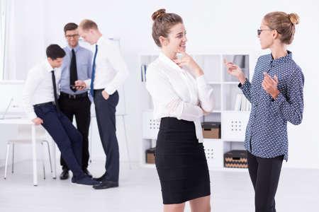 acoso laboral: Dos trabajadores de la oficina de las mujeres chismosas, de pie en una oficina de la luz, en el fondo de tres hombres que miran algo en un smartphone Foto de archivo