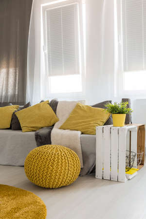 living room window: Light new style living room with window, sofa, DIY side table, yellow pouf, carpet and pillows