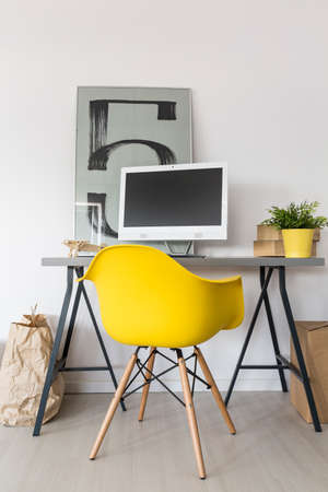 simple: Simple home office with desk, yellow chair, computer and decorative modern painting on the wall Stock Photo
