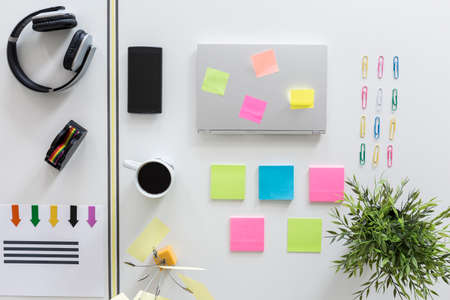 ordered: Desktop with esthetically ordered statiorery, clips, multicoloured sticky notes and laptop