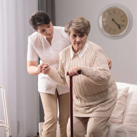 helping up: Young caregiver helping older lady to stand up Stock Photo