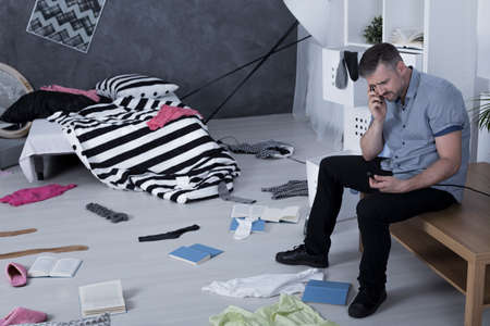 chaos: Room after burglary and despair man calling police