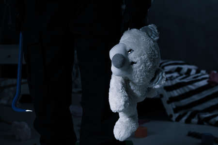 burglar protection: Kidnapper holding a teddy bear and a crowbar, standing at night in a childs room