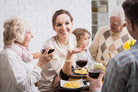 mother in law: Shot of a cheerful young woman at a table surrounded by her family members