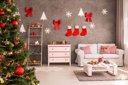Modern and spacious living room with decorated Christmas tree and DIY wall decor