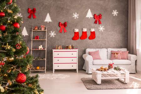 Moderne en ruime woonkamer met versierde kerstboom en DIY-wanddecor