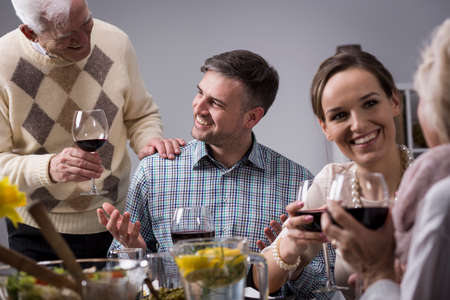 father in law: Portrait of a young, laughing man having a family dinner, with family members drinking wine and chatting