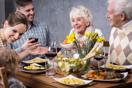 mother in law: Whole family gathered at the dinner table, laughing and enjoying their time