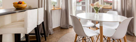 dining table and chairs: View of the kitchen island and a white dining table with chairs