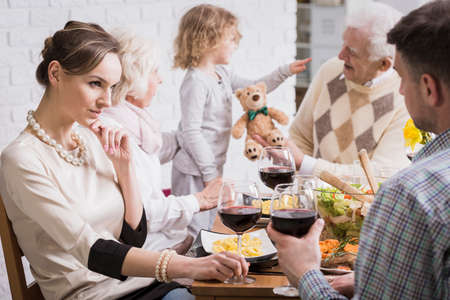 mother in law: Shot of a family dinner with a young couple in the foreground