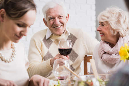relatives: Portrait of a cheerful elderly man holding a glass of wine during a family dinner, surrounded by his relatives Stock Photo