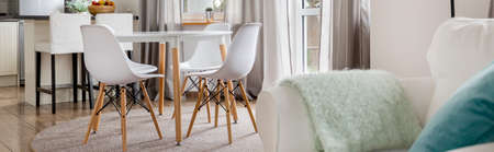 dining table and chairs: Part of open space in home with dining table with chairs and window with curtains Stock Photo