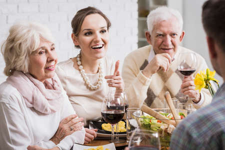 mother in law: Cheerful family members drinking wine and chatting during an elegant dinner