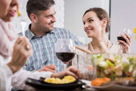 supper: Affectionate portrait of a young couple smiling at each other and drinking wine at a table Stock Photo