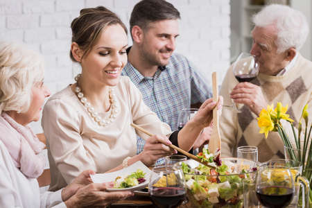 mother in law: Young woman in a cocktail dress at a dinner table with her family, serving salad to her mother-in-law