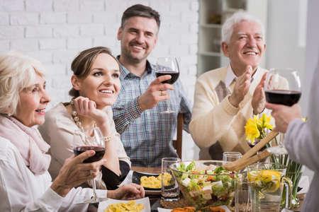 comida de navidad: Familia en la mesa haciendo un brindis con vino y escuchar un discurso tostadas