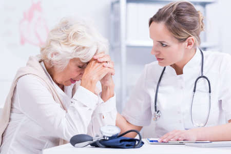 unease: Doctor looking at the elder patient full of unease