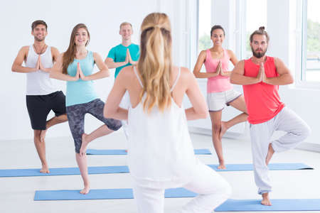 in unison: Women yoga trainer standing on one leg in front of yoga practitioners group