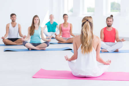 in unison: Meditation trainer giving the instructions to the yoga practitioners sitting on foam pads
