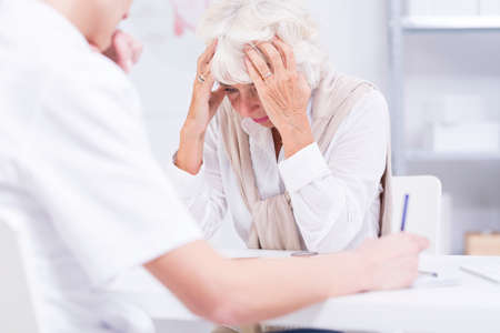 unease: Elder woman alarmed by her health state, sitting in a doctors office Stock Photo